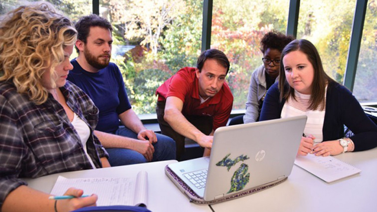 Students with mentor focused on computer