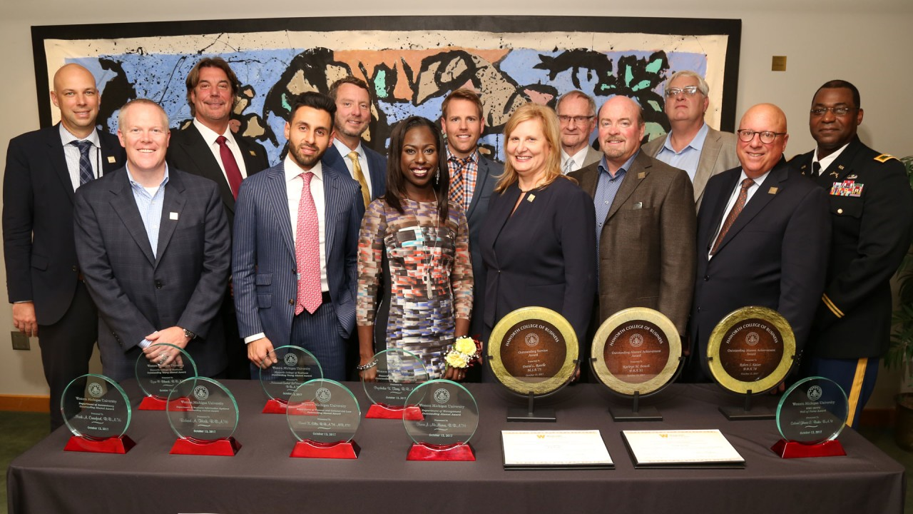Award recipients in the dean's conference room with trophies from 2017 alumni award ceremony.