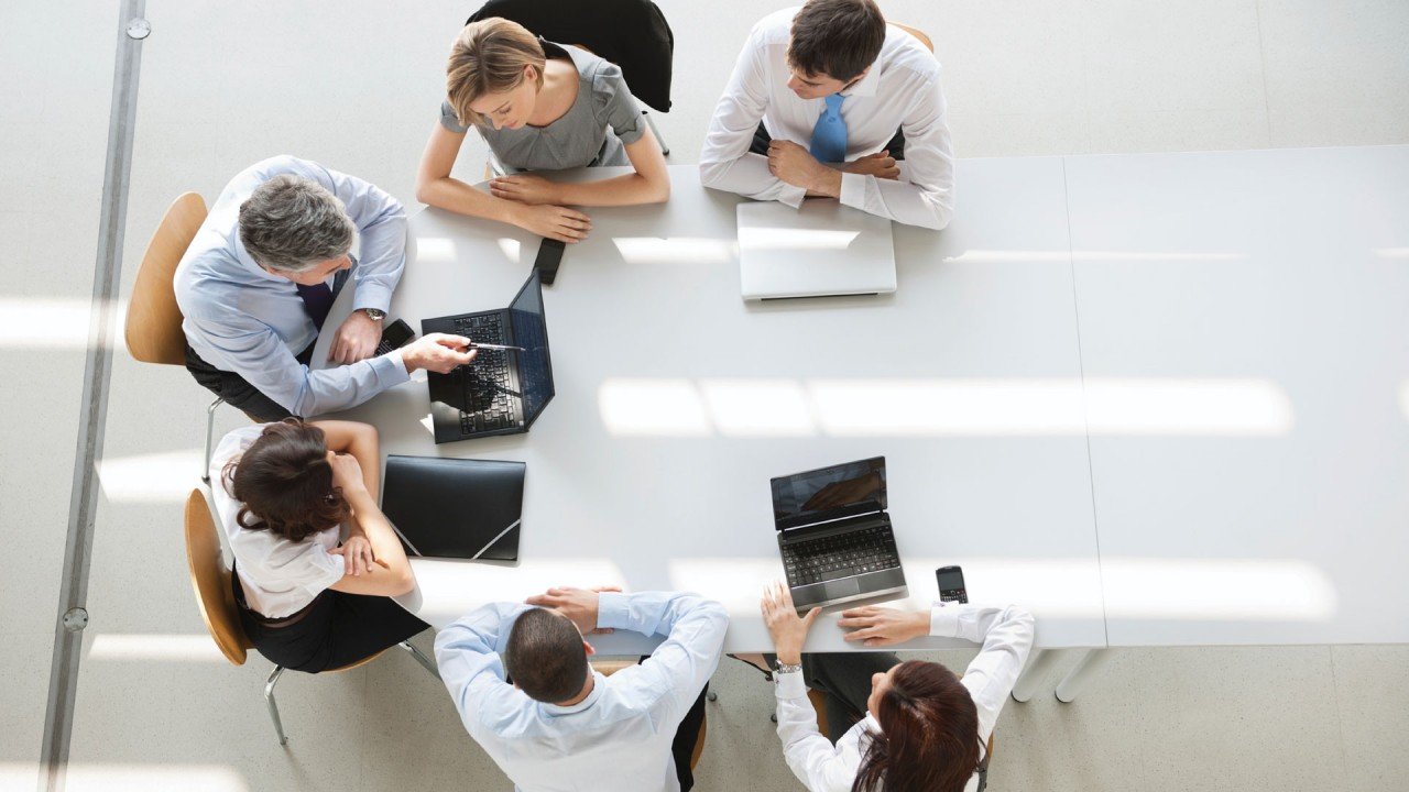 Six people sitting at a conference table working