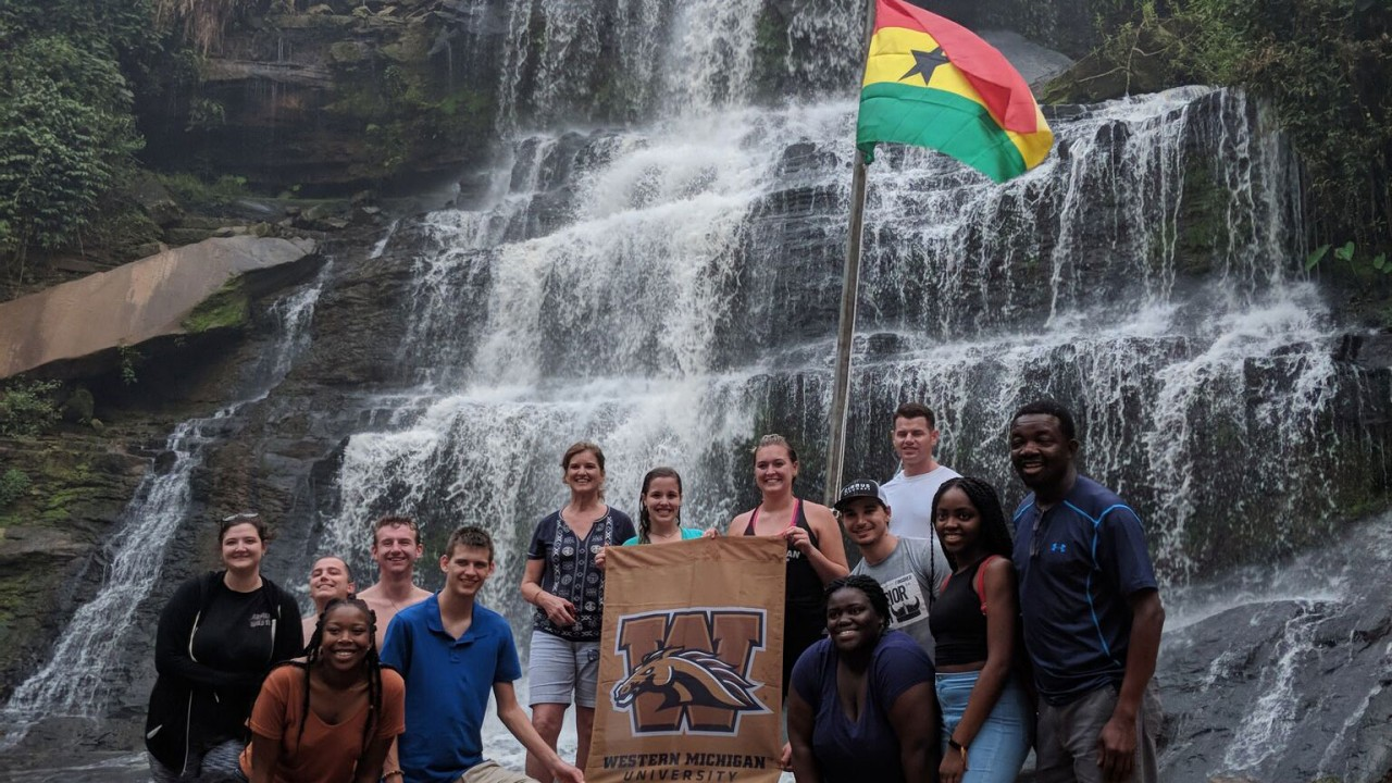 Students and professor holding a WMU flag in front of a giant waterfall in Ghana.
