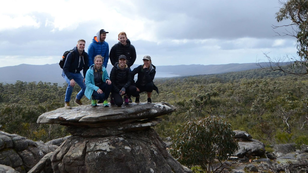 Six students atop a flat rock at the peak of a hill.