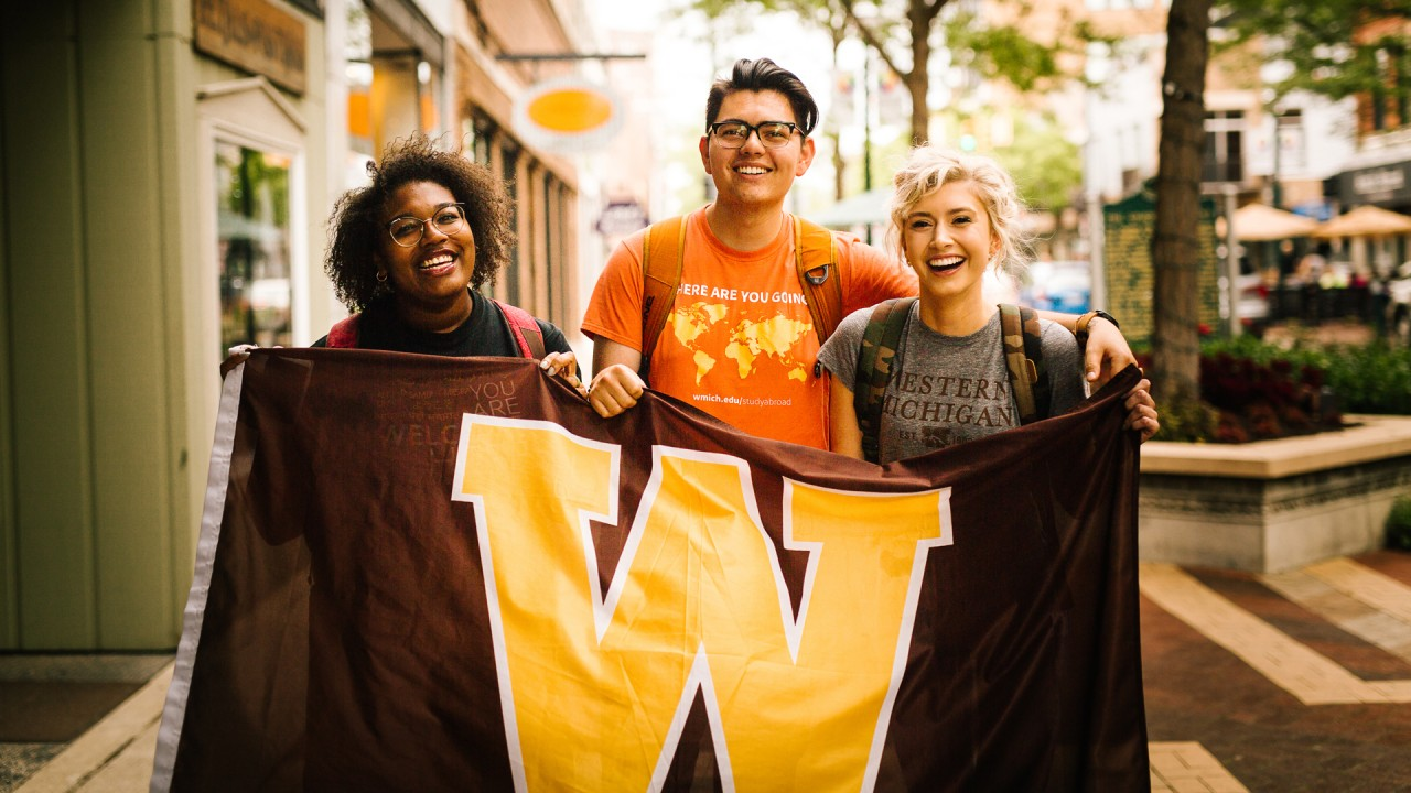 Three students smiling and holding a Western Michigan University flag.