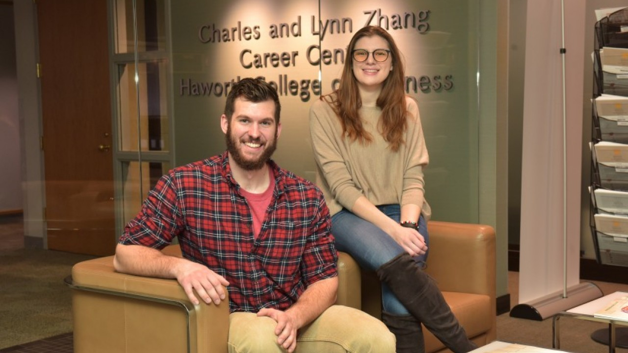 Two students in casual attire sitting in front of the Zhang Career Center sign in Schneider Hall.