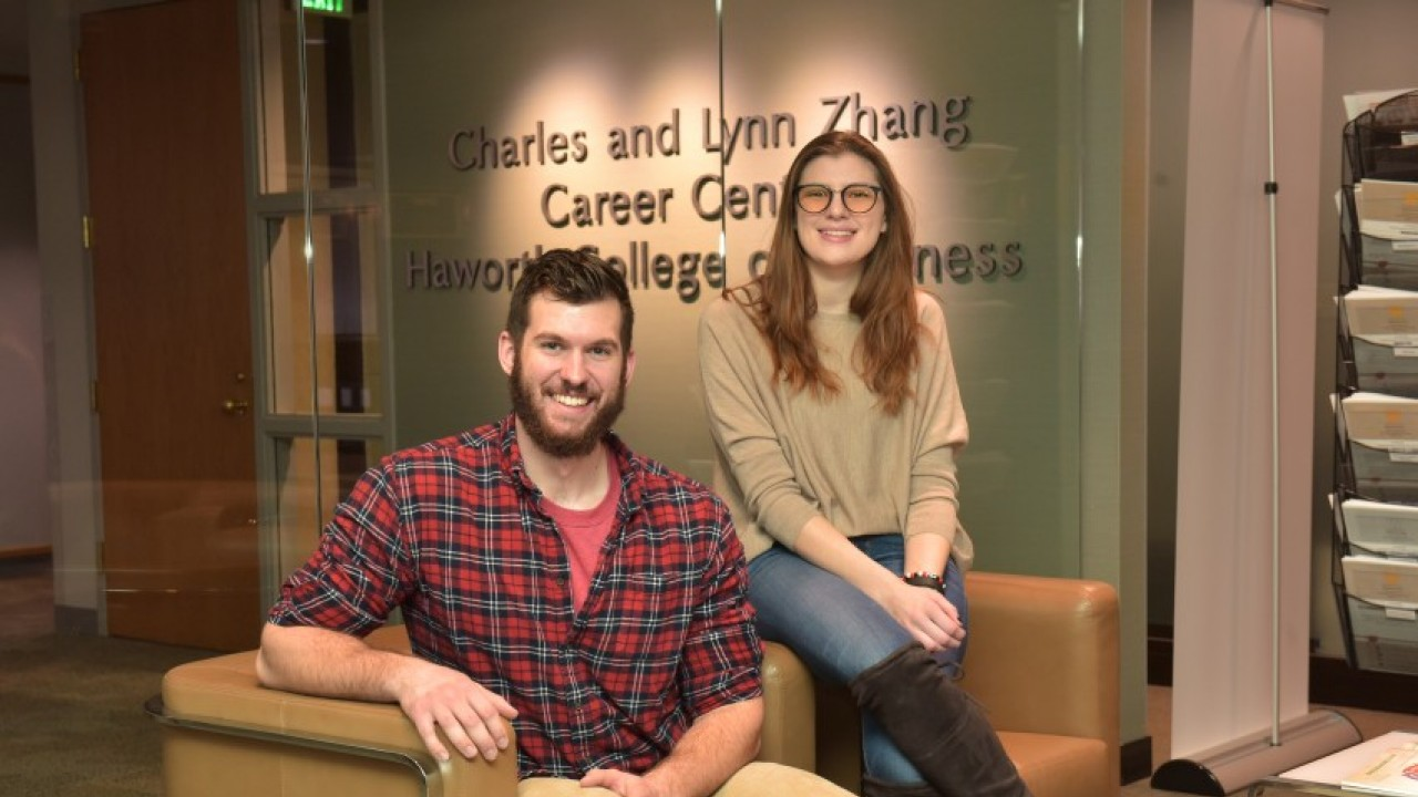 Two smiling students sitting in career center in front of Zhang Career Center sign.