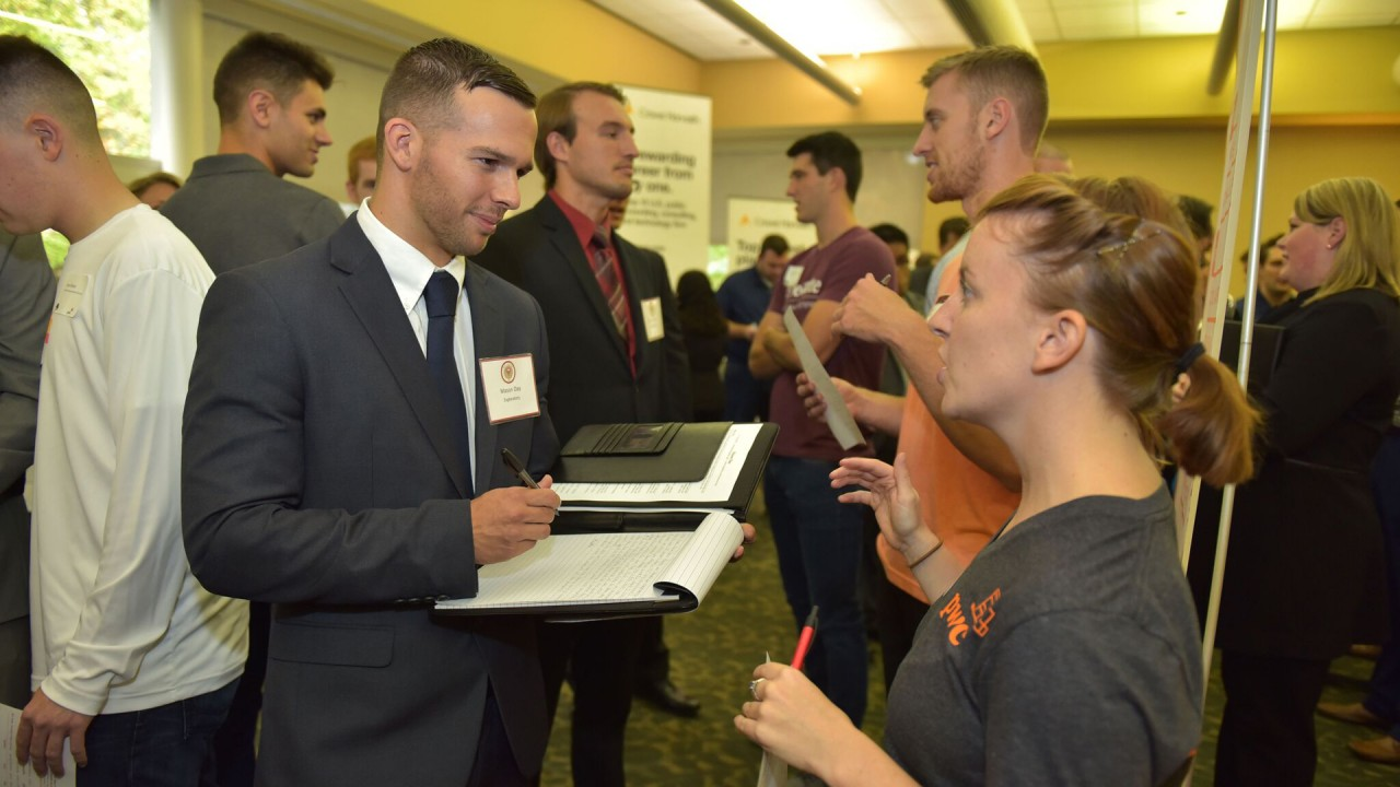 Student in professional dress speaking with a recruiter during career fair.