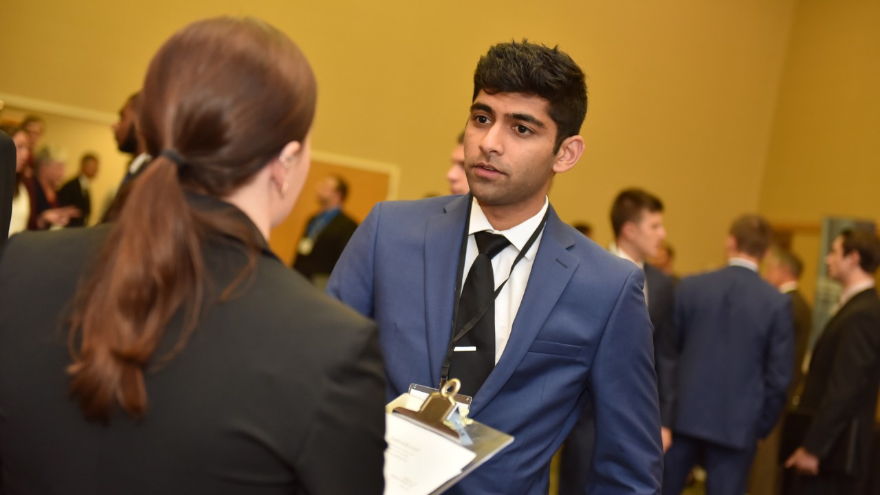 A student in professional dress speaking with a recruiting representative during a finance career event.