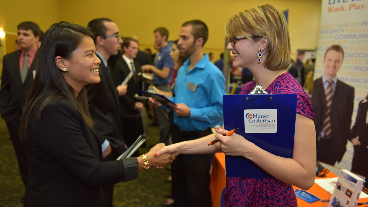 Two women shaking hands at career fair. One is a student and one is a recruiter.