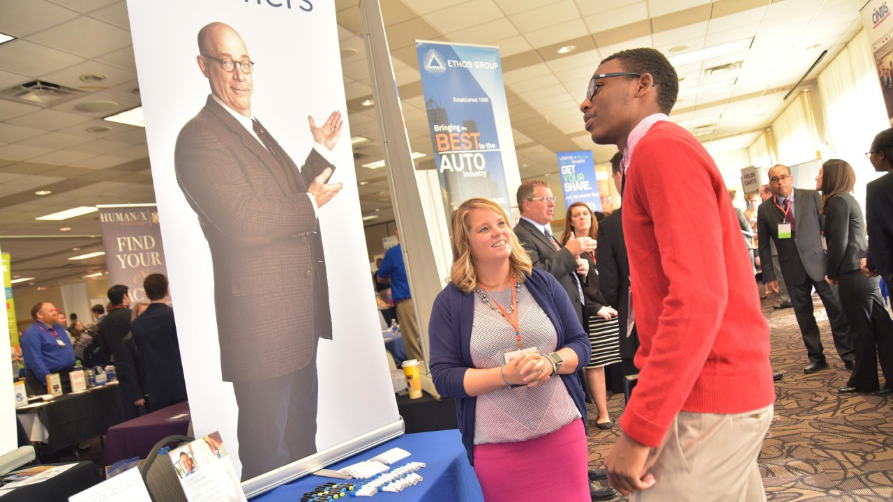 Student and recruiter talking at career fair.
