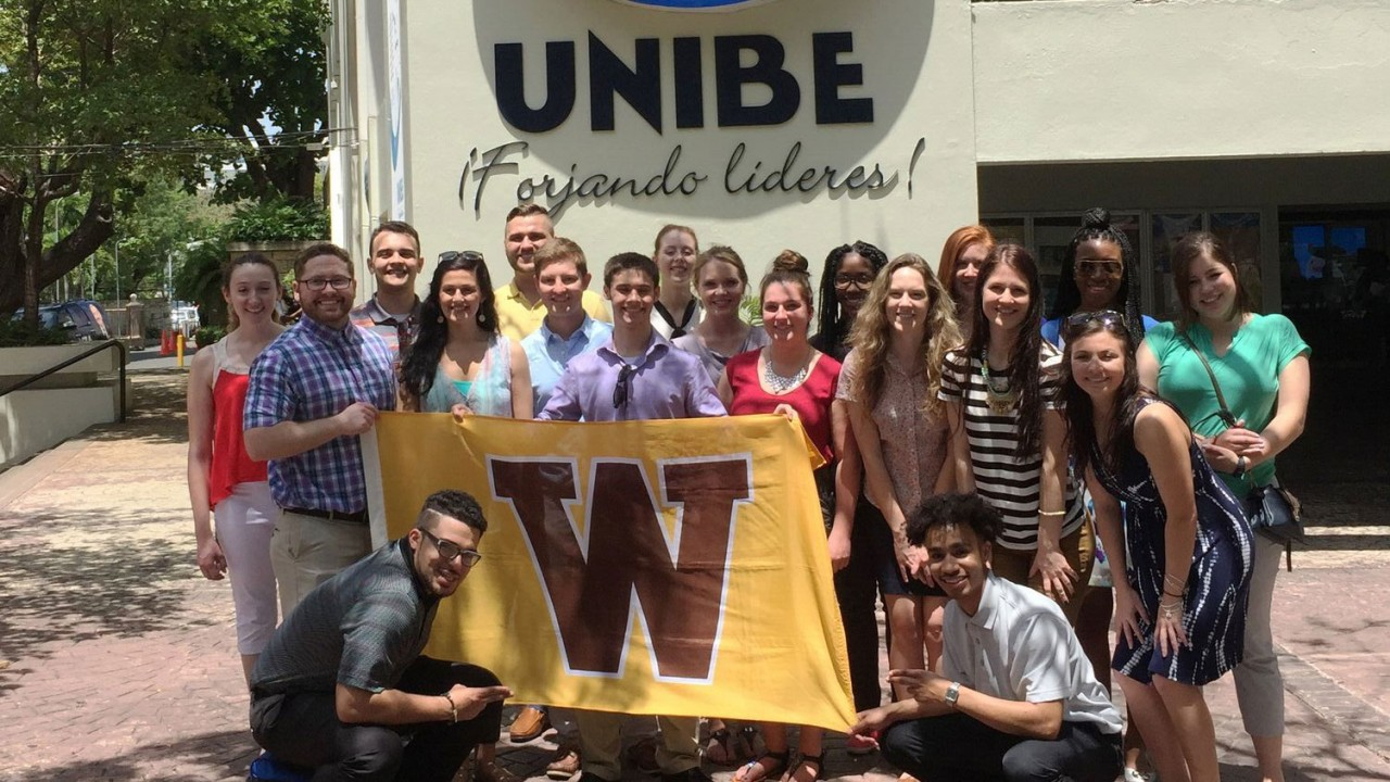 Students holding the W flag in front of the UNIBE sign and building.