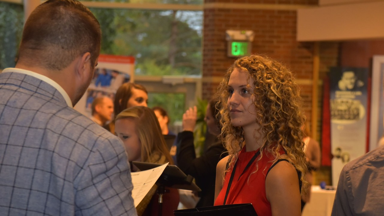 Female student in professional dress speaking with a recruiting during a career fair.