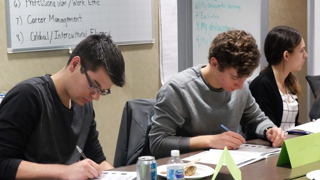 Three students working in the conference room of the Zhang Career Center during a workshop.