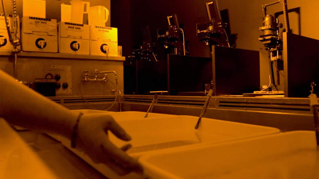 A student's hand tilts a tray in the photography darkroom.