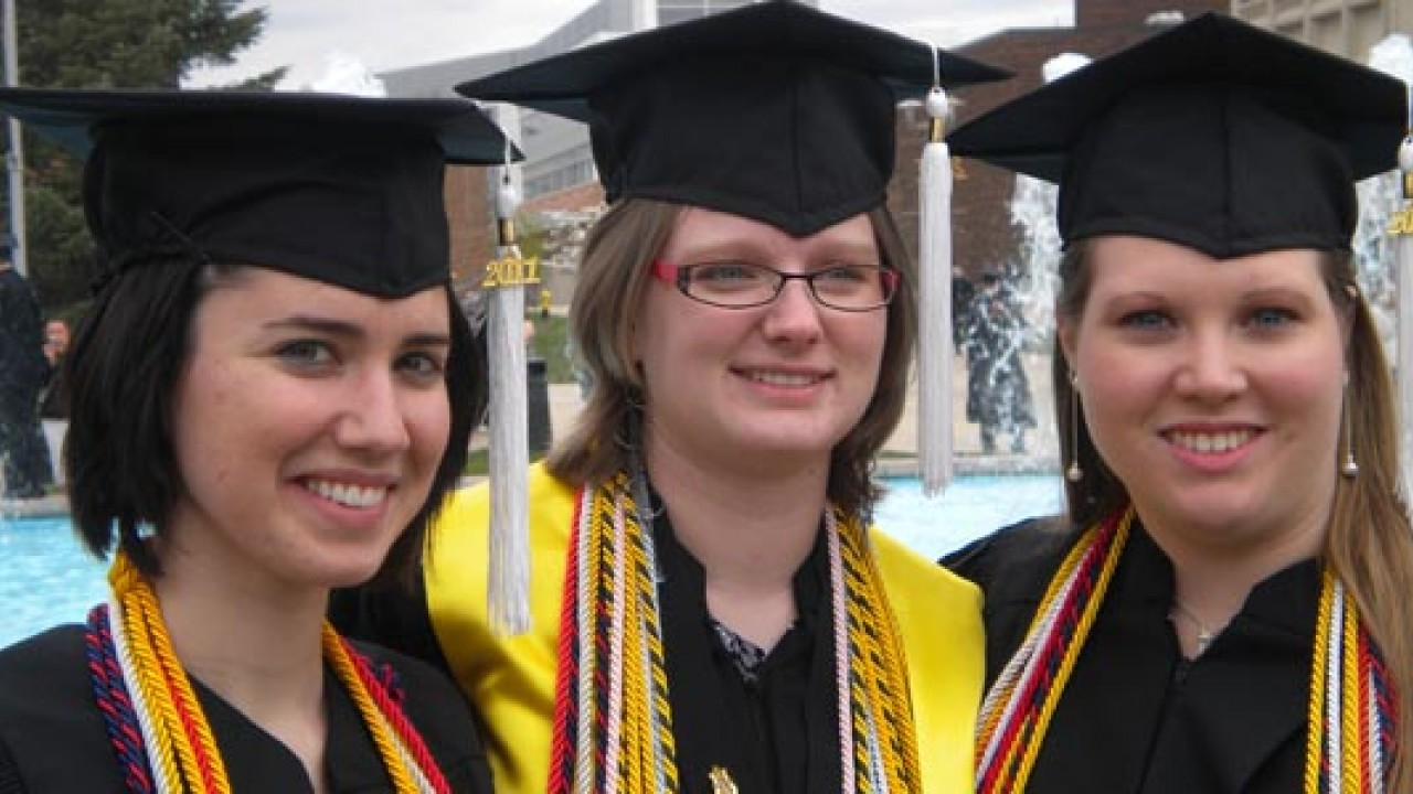 A photo of three female honors college graduates in front of the fountain.