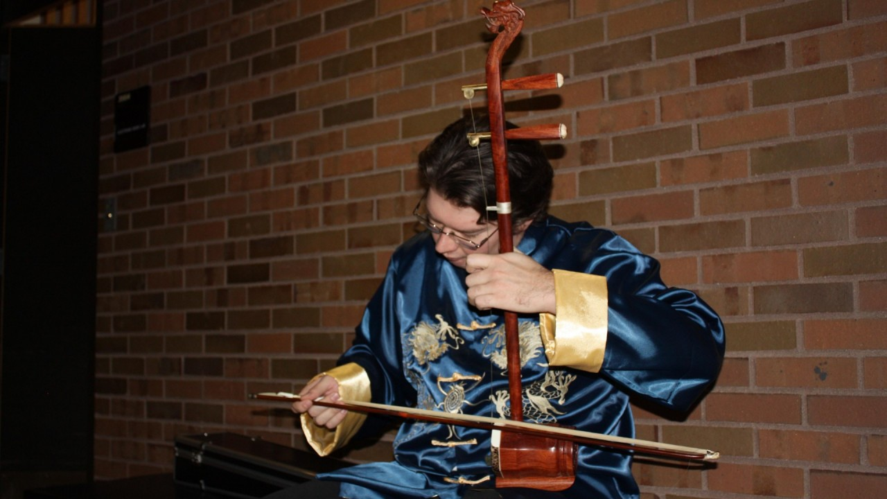 Photo of a student playing an instrument.