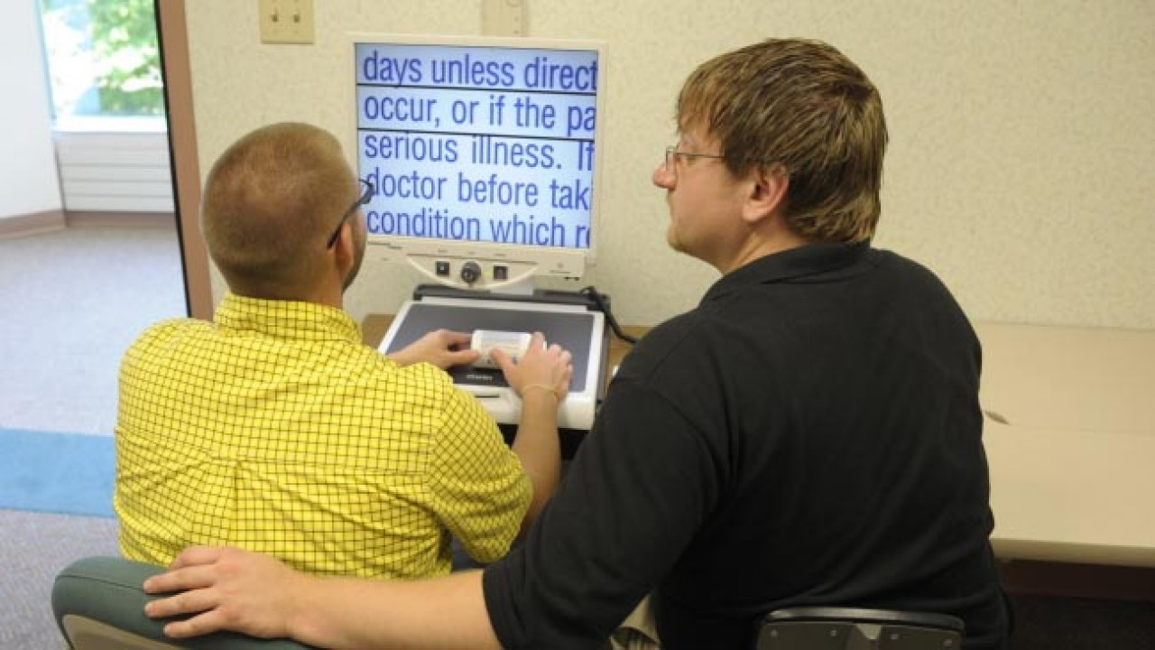 Two men using a text enlarging machine.