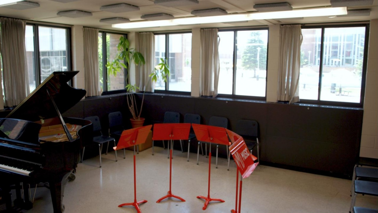 Photo of the chamber music room which has many windows facing a fountain with a small grand piano and five music stands in a semi-circle