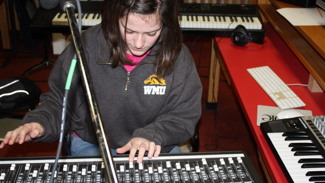 Photo of a girl using a sound mixing board.