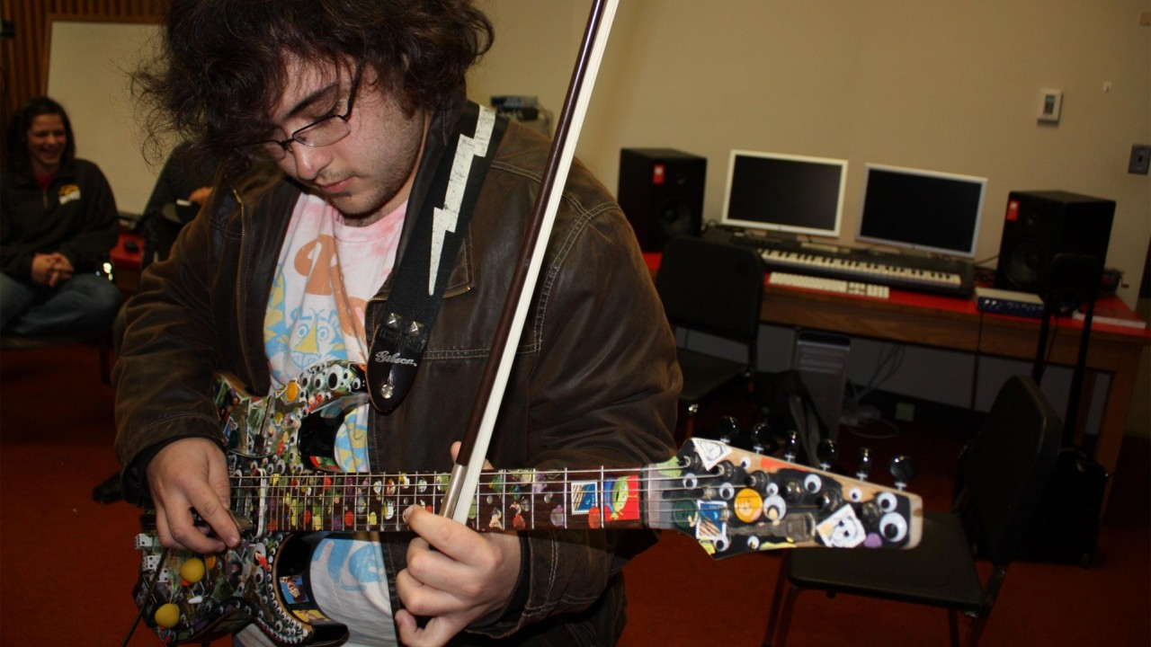Photo of a student playing electric guitar with a bow.