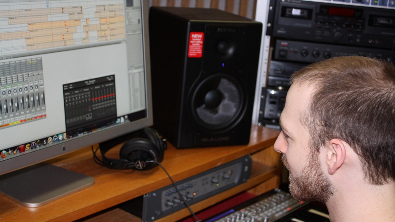 Photo of a student using music mixing software on a computer.
