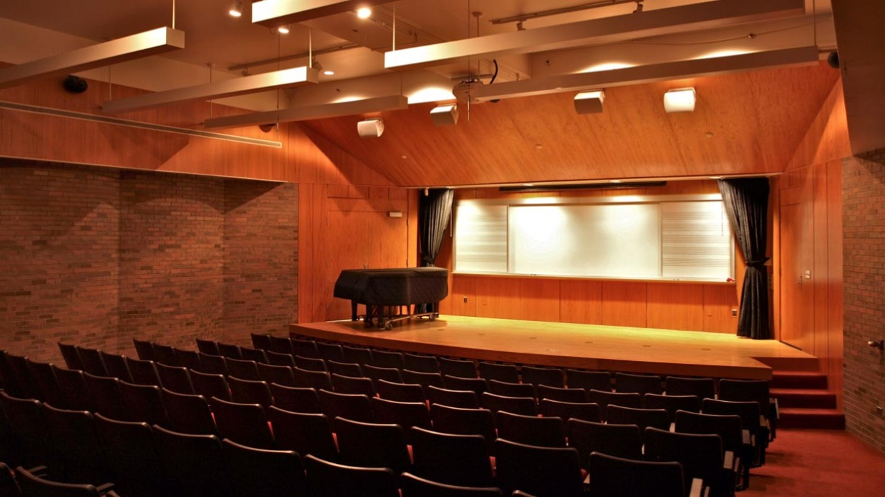Photo of a teaching lecture hall with a projector and white board with music staff
