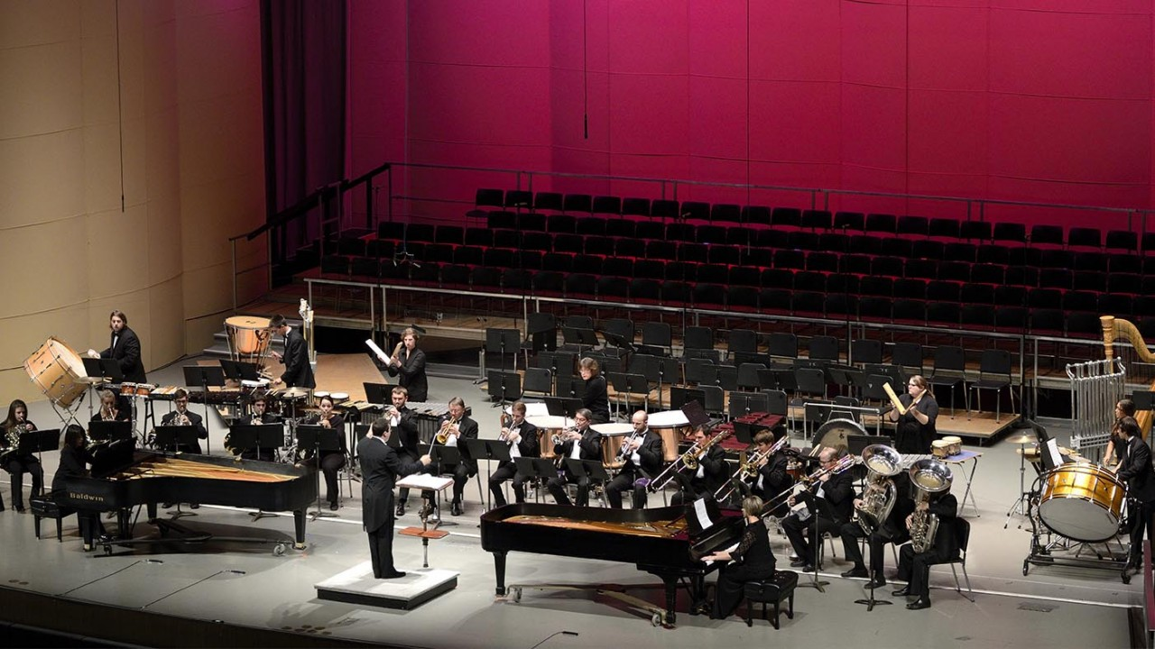 Photo of a chamber wind ensemble performing on Miller Auditorium's stage with red back lighting