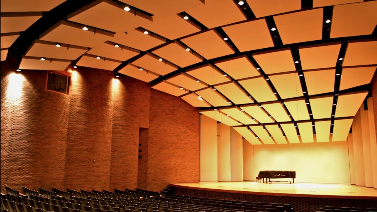 Photo of the recital hall with a grand piano center stage with an empty audience
