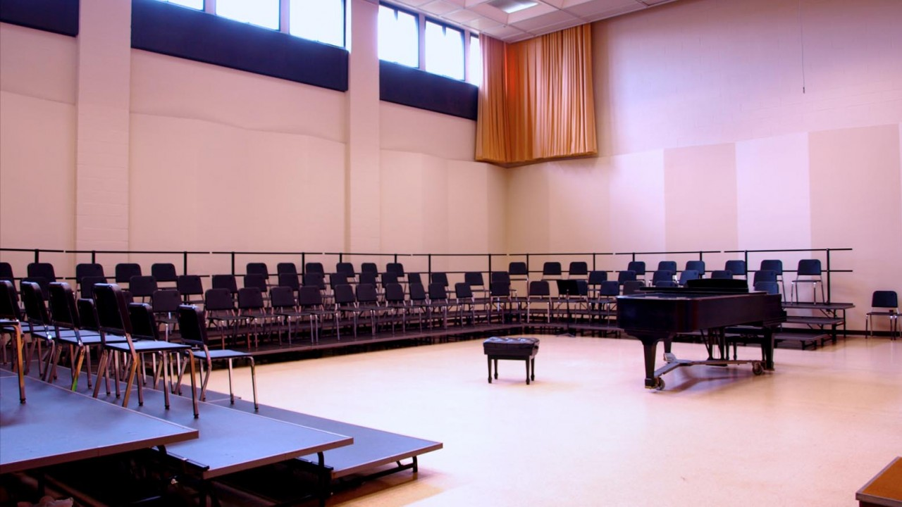 Photo of a choral rehearsal room with a grand piano in the middle of the room surrounded by choral risers