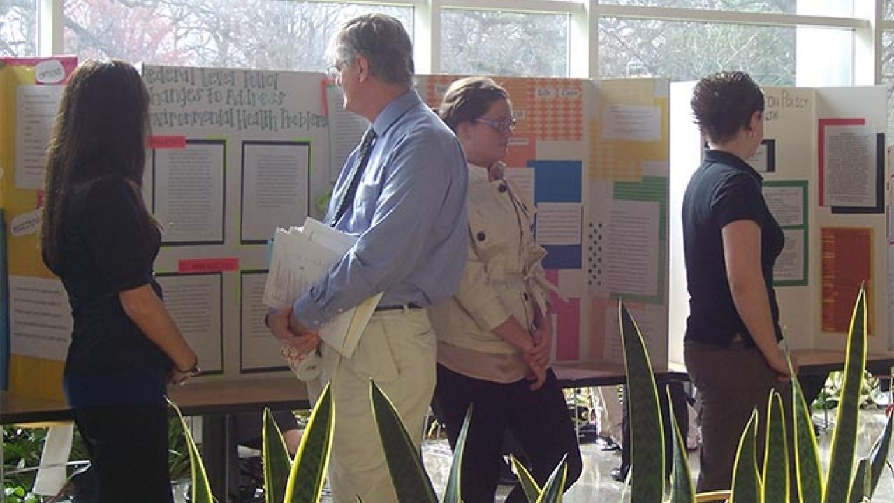 People looking at student projects on display