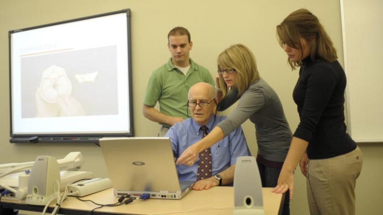 Students and professor collaborating around a computer.