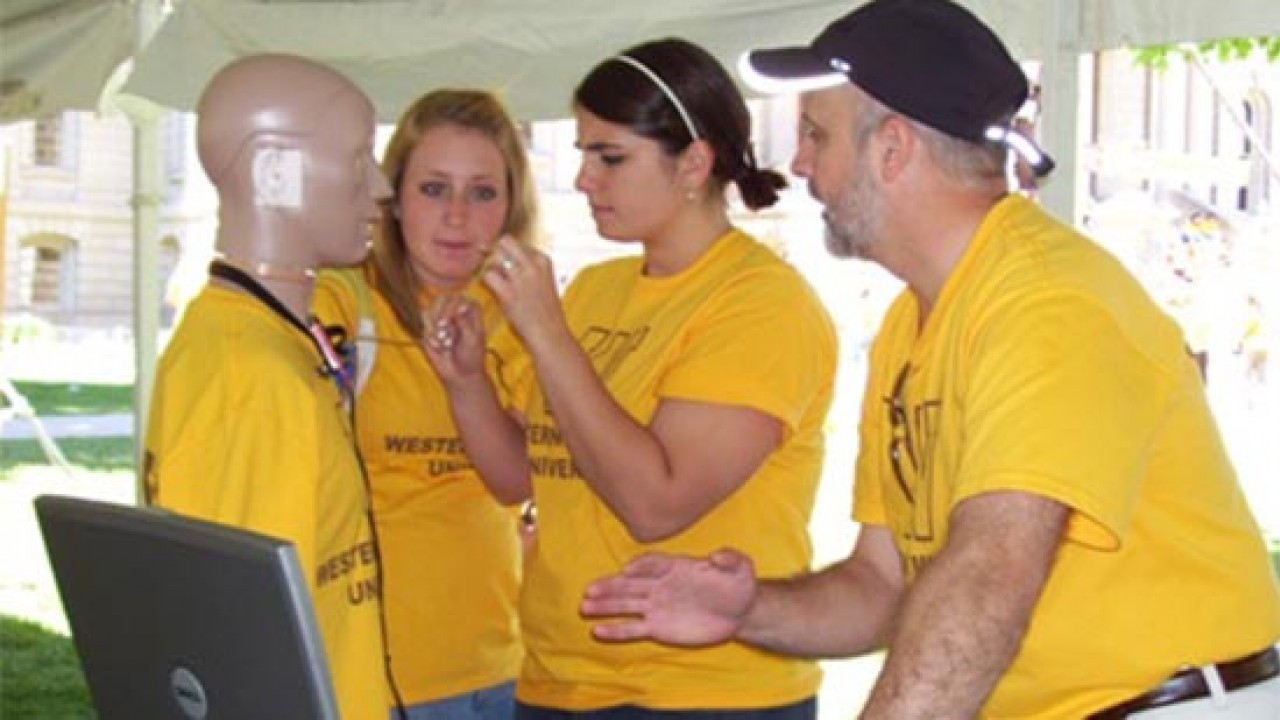 Students and instructor hooking a test dummy up to equipment.