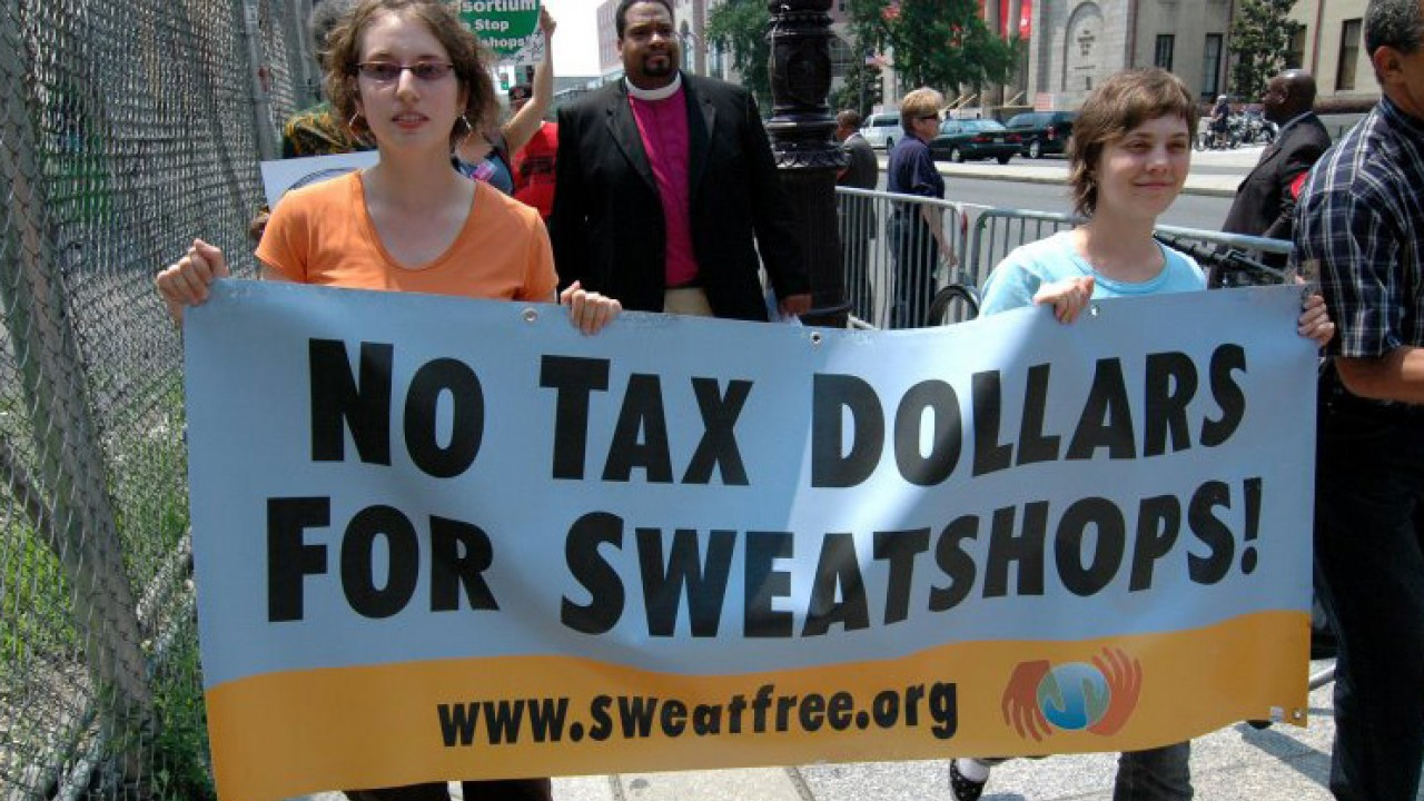 "Two women walking with a sign that says ""no tax dollars for sweatshops!"""