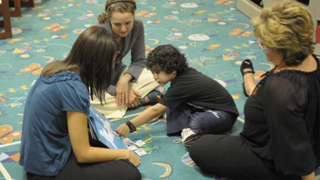 Three women reading a story with a little boy.