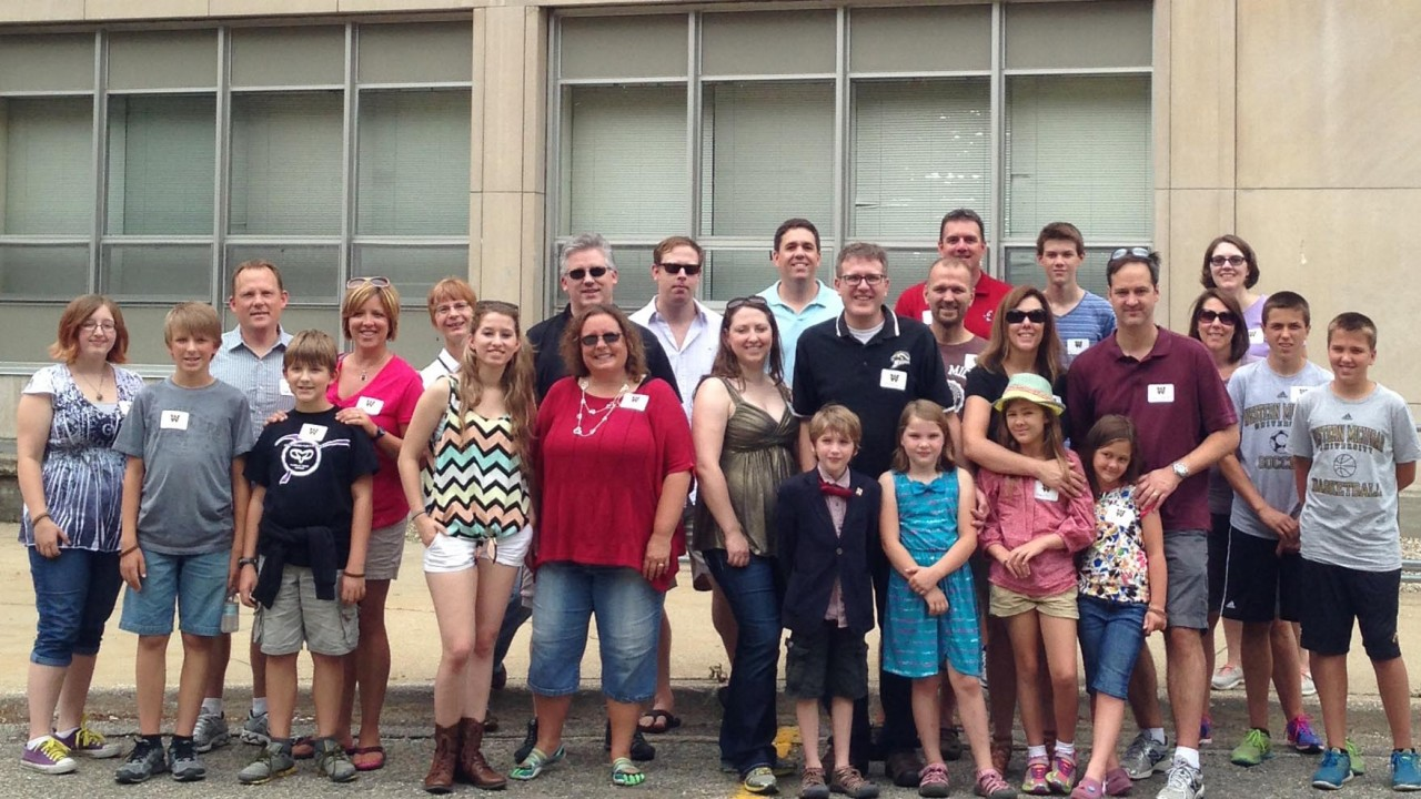 Group of honors college alumni and their families standing in front of a building.