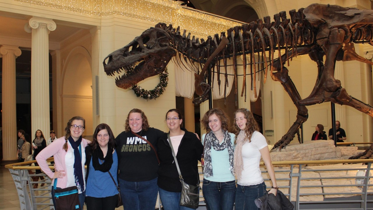 Honor students posing in front of dinosaur skeleton at the Field Museum in Chicago.