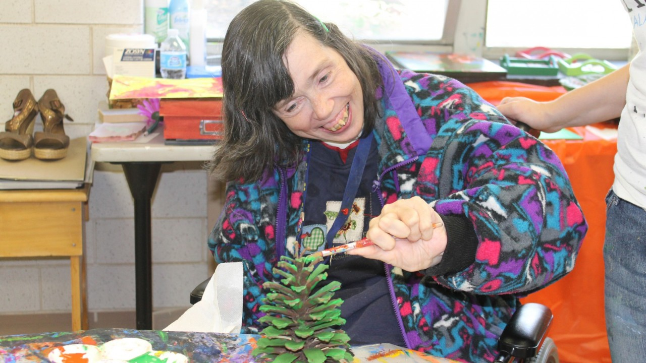Photo of a woman painting a pine cone.
