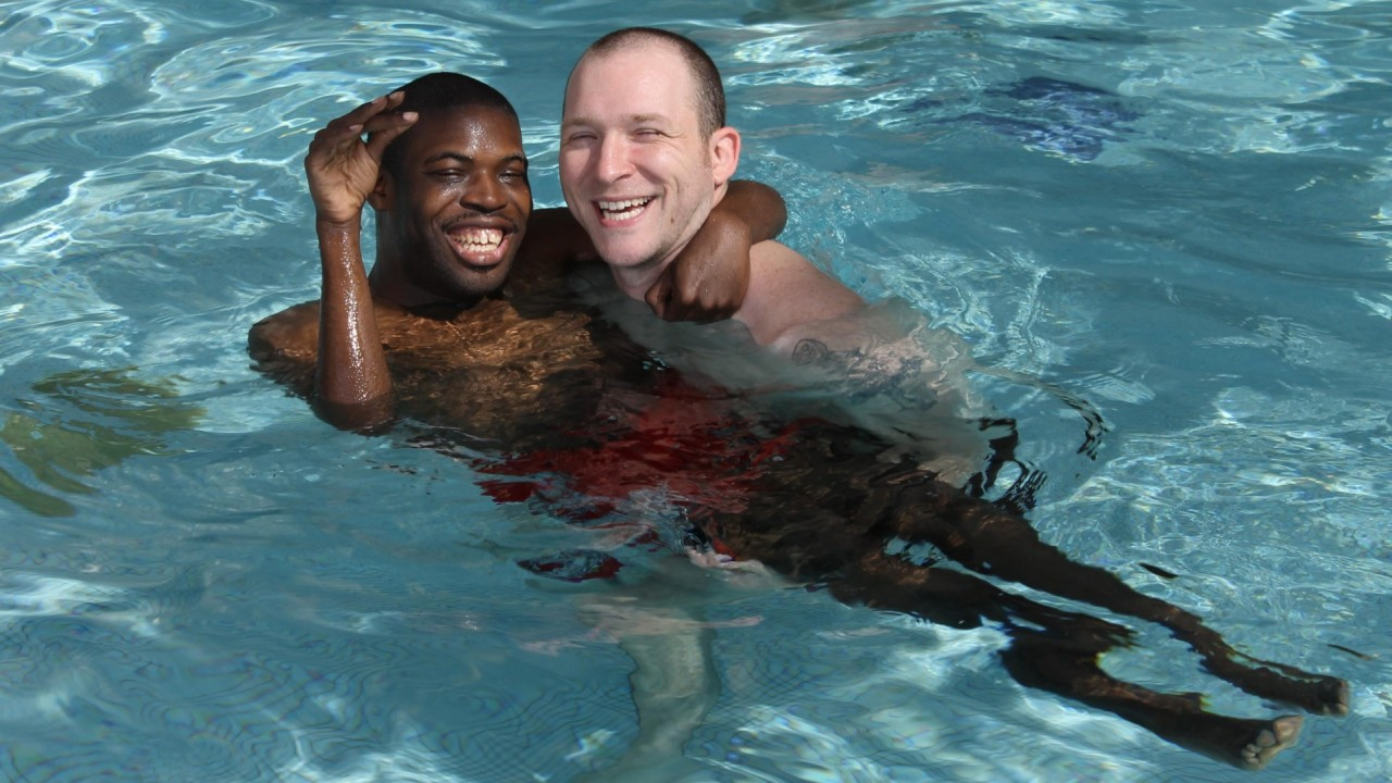 Photo of two men swimming in a pool.