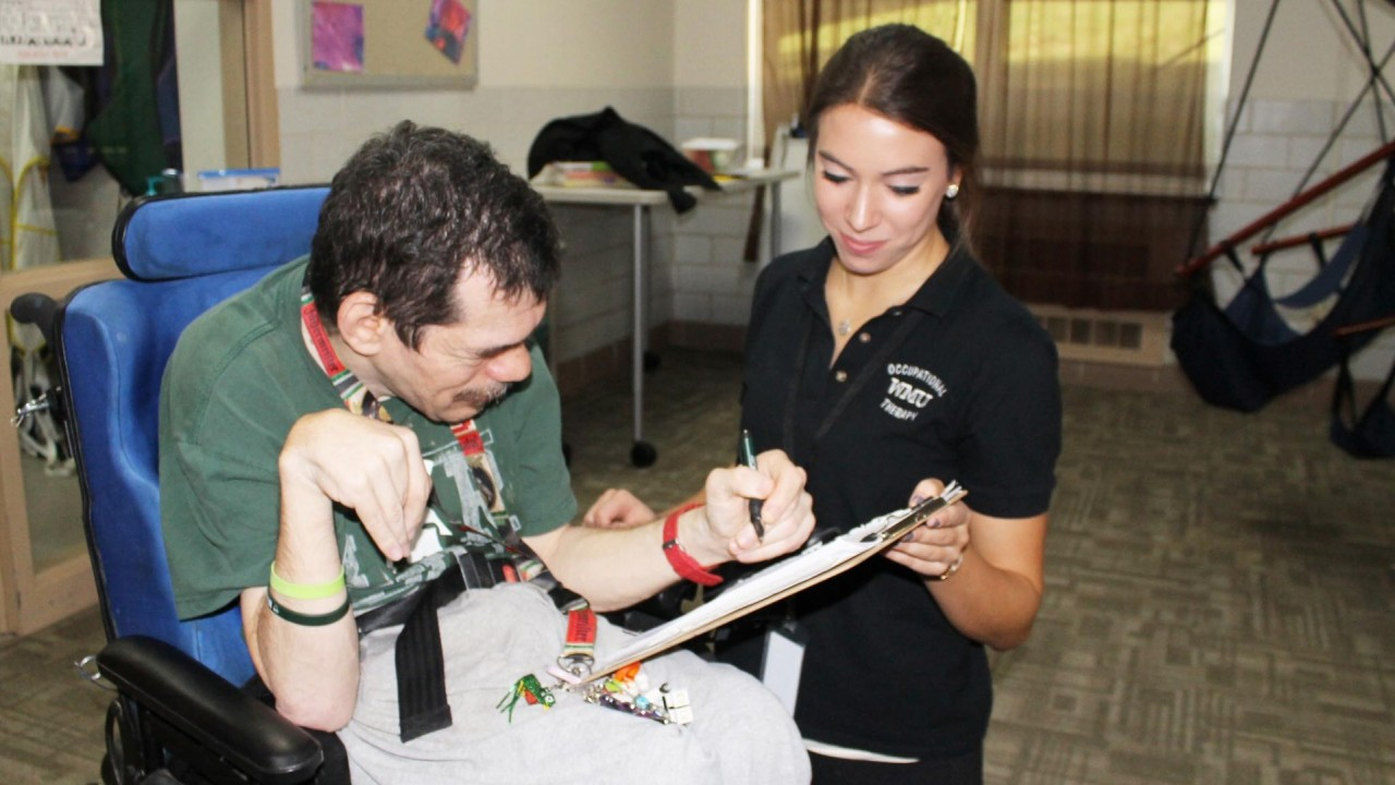 Photo of a women helping a man with a form.