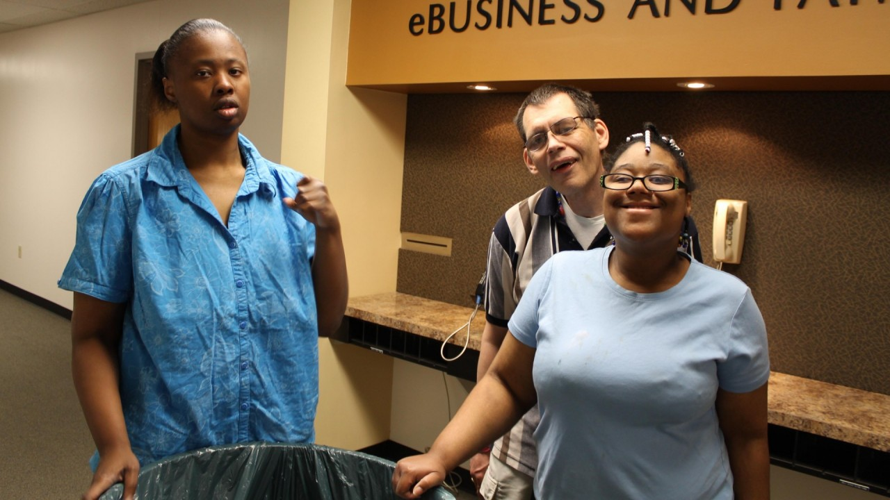 Photo of three people gathering recycling.
