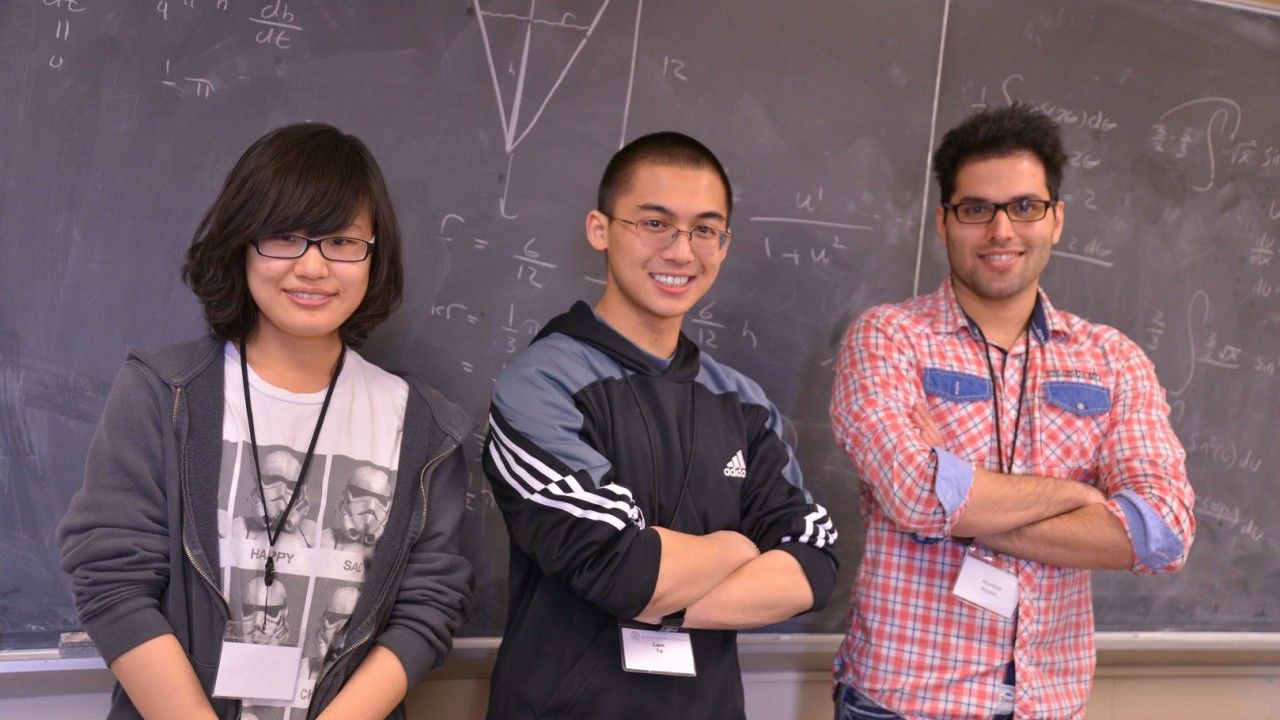 Students pose in front of chalkboard.