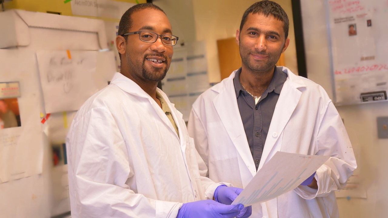 Two male students in lab coats.
