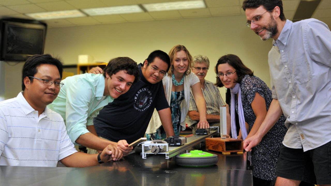 Students conducting dynamics experiment at a table