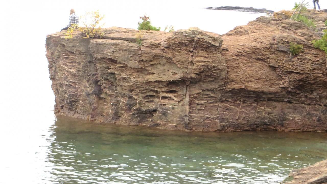 Student on rock ledge overlooking lake.