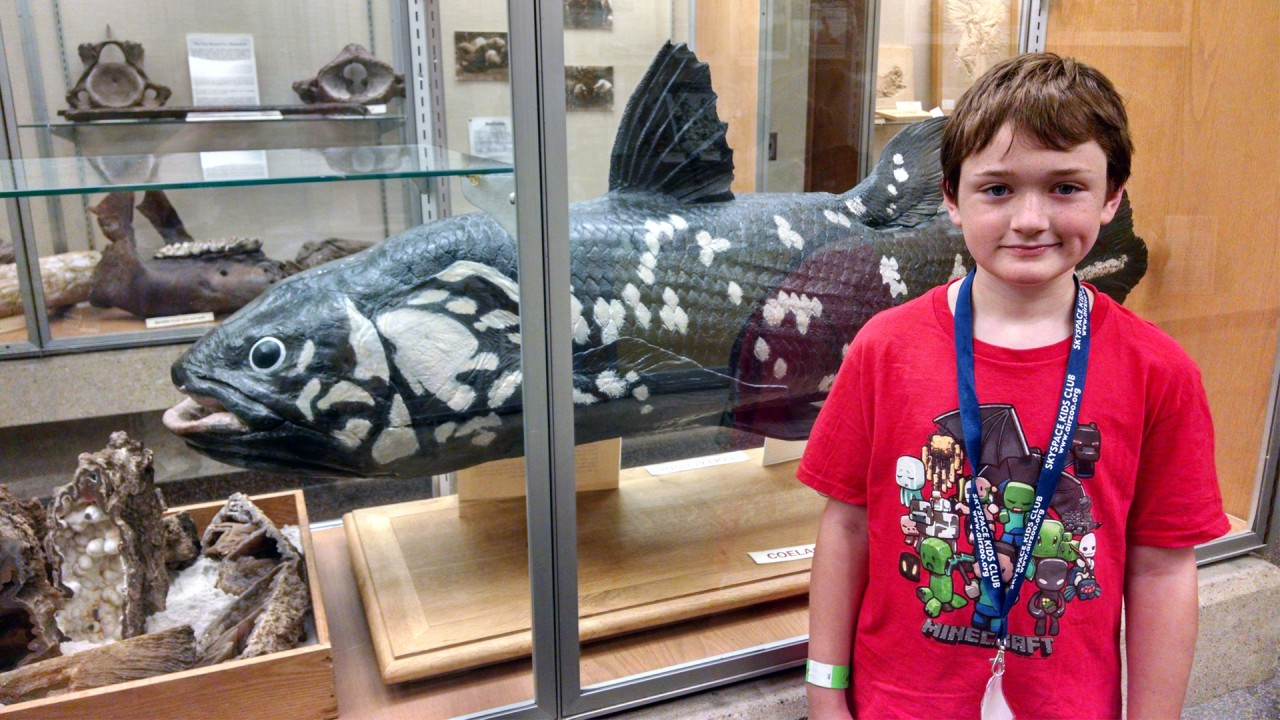 A young student stands near a coelacanth cast