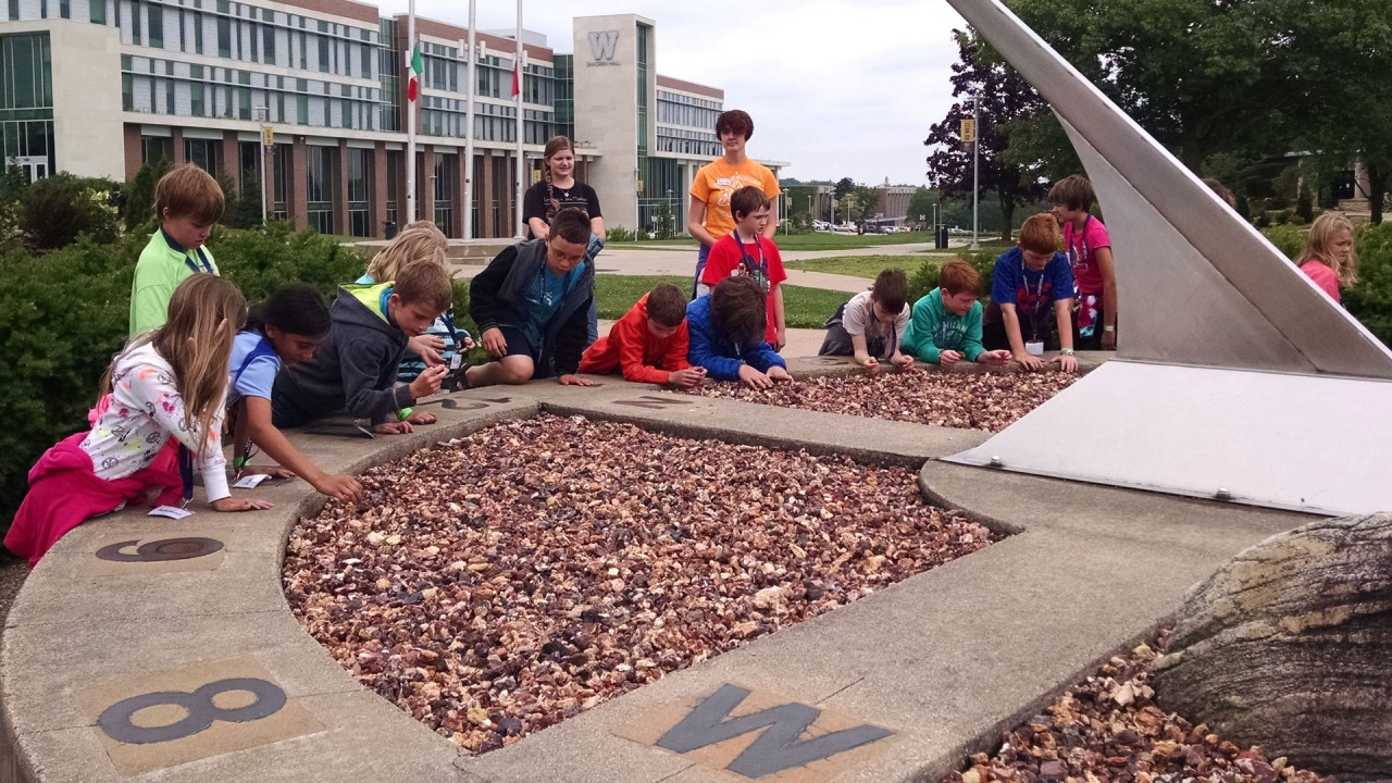 A group of young students explore a sundial