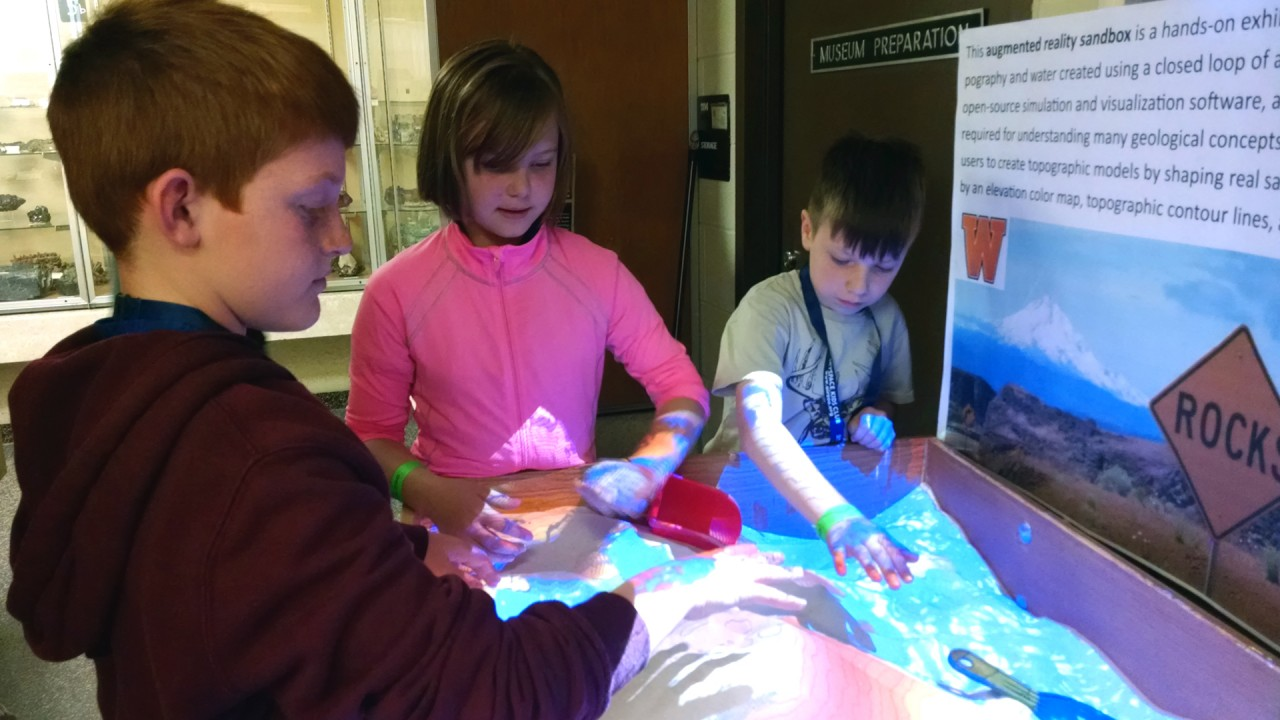 Young students explore the augmented reality sandbox