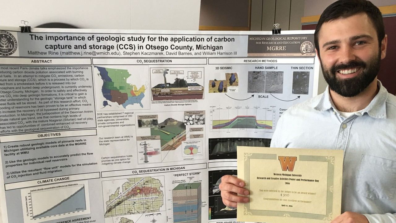 A graduate student with his research poster