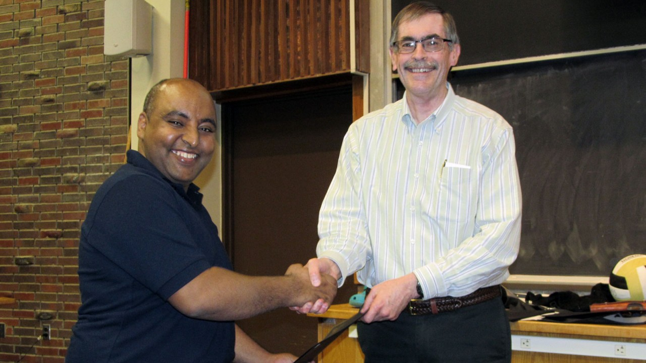 A graduate student receives an award from a faculty member