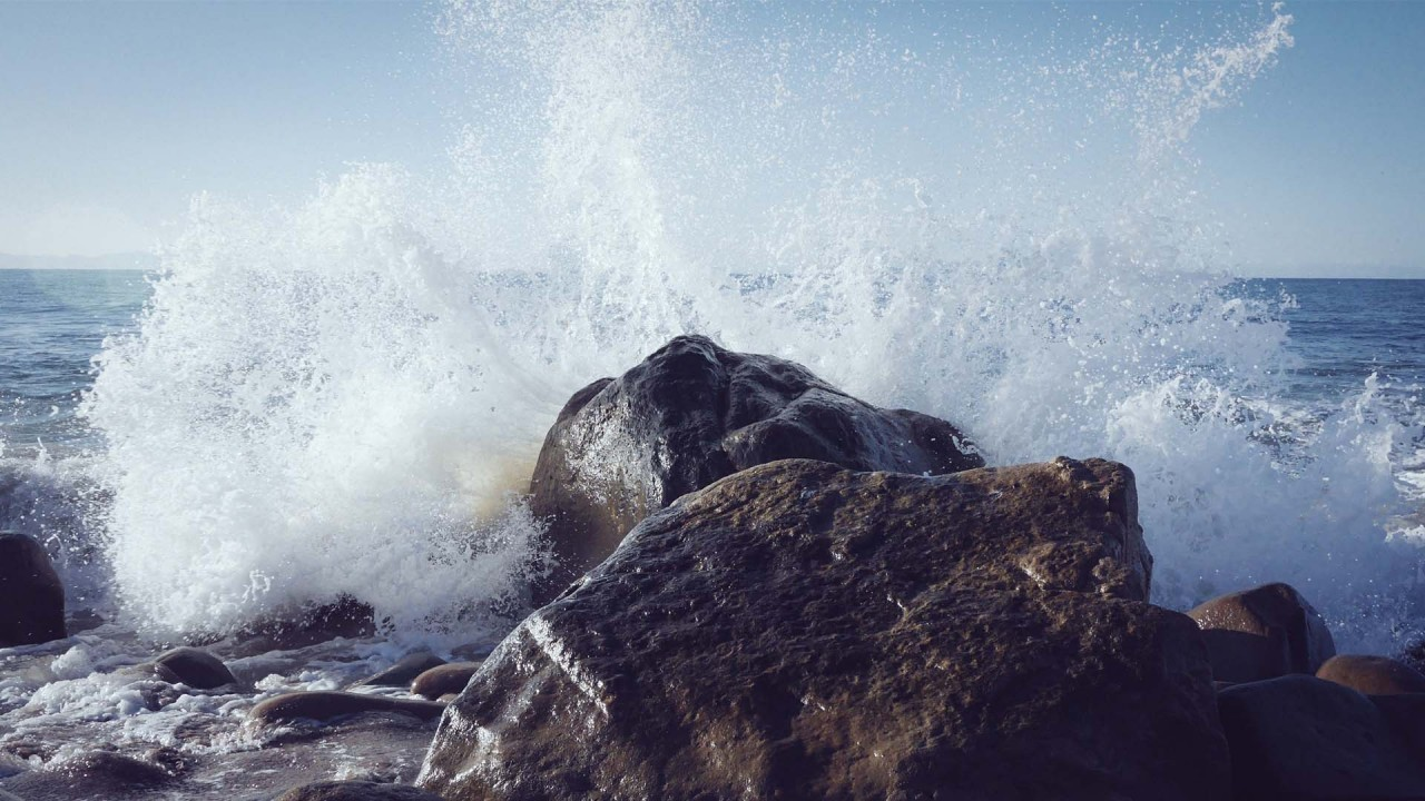 Ocean waves splashing aginst a rock outcropping