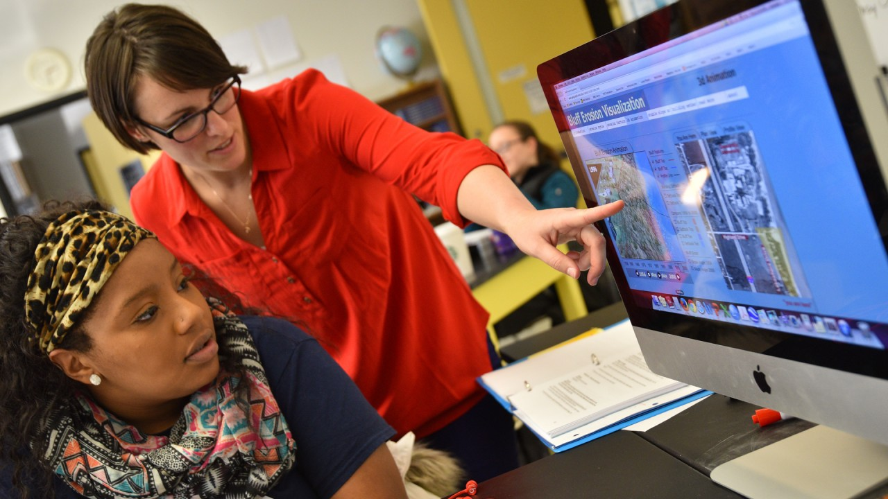 A TA demonstrates a concept to a student using a computer simulation