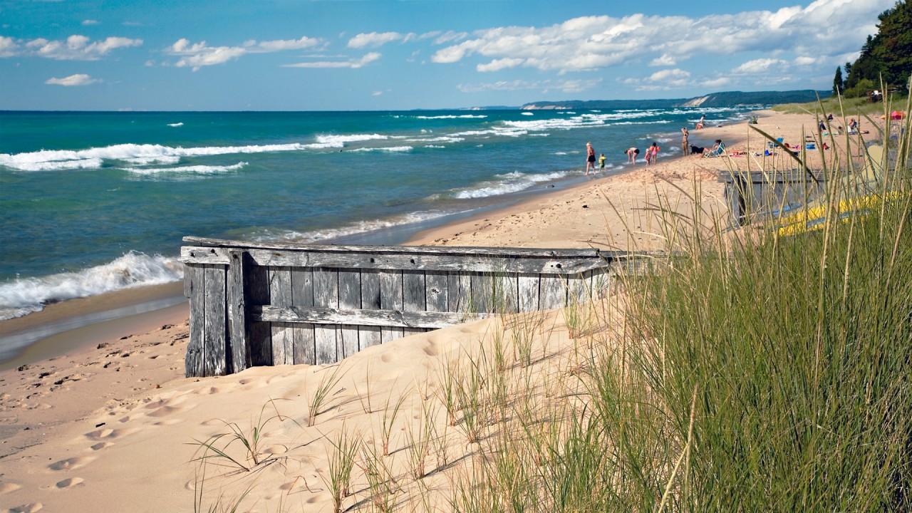 A Lake Michigan beach with people swimming along shoreline
